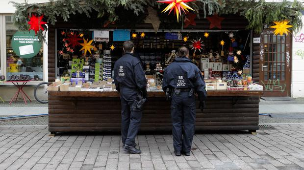 German police talk with a vendor at the Christmas market a day after the package containing nails was found in Potsdam Photo: AP