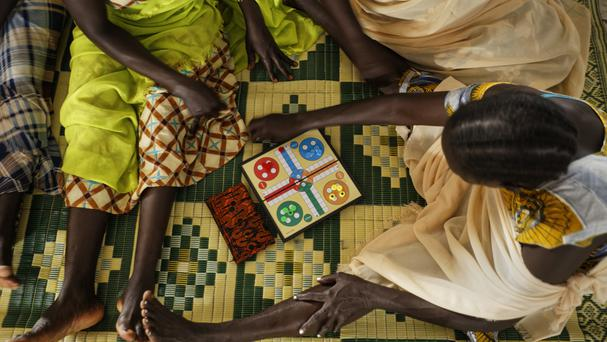South Sudanese refugee women playing a board game (AP)
