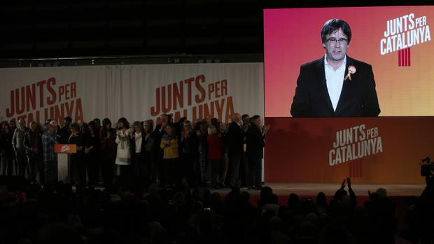 Ousted Catalan president Carles Puigdemont appears on a giant screen during a Catalan regional election event (Manu Fernandez/AP)