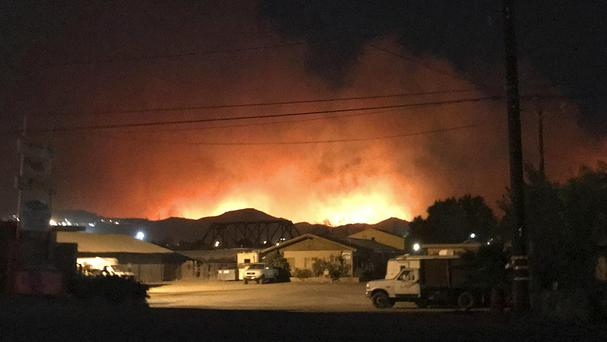 Flames from a wildfire loom up over a neighbourhood in Santa Paula, California (Megan Diskin/The Ventura County Star via AP)