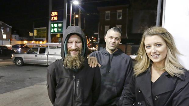 Johnny Bobbitt Jr, left, Kate McClure, right, and Ms McClure's boyfriend Mark D'Amico at a Citgo station in Philadelphia (Elizabeth Robertson/The Philadelphia Inquirer via AP, File)