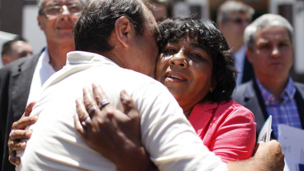 Norma Gomez, sister of fallen soldier Eduardo Gomez, is embraced outside the National Memory Archive after being notified that her brother's remains, buried in an anonymous grave, have been identified, in Buenos Aires, Argentina (AP)