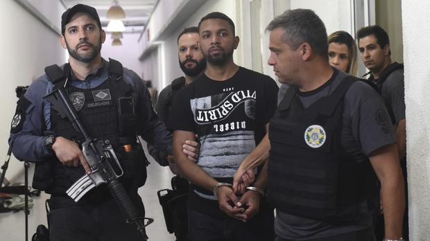 Drug boss Rogerio Avelino da Silva is escorted by police officers in Rio de Janeiro (Fabio Teixeira/AP)