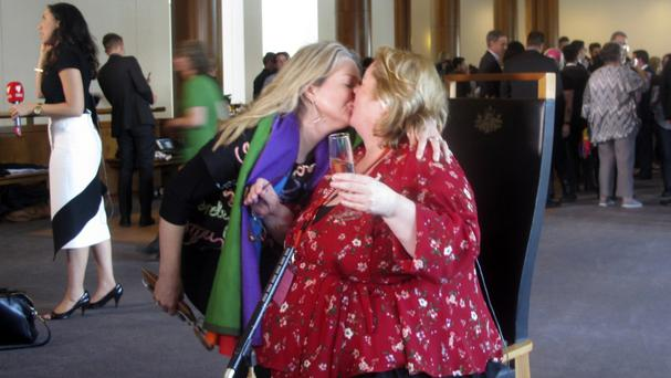 Australian senator Louise Pratt, left, kisses actress Magda Szubanski at Parliament House in Canberra (Rod McGuirk/AP)