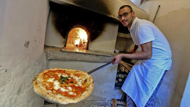 A man shows a pizza cooked in the first stone oven which was used in 1889 to make the first pizza Margherita in Naples (Ciro Fusco/ANSA Via AP)