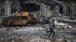 A boy rides his bike past destroyed cars and houses in a neighbourhood of Mosul liberated by Iraqi security forces (Felipe DanaAP)
