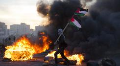 A Palestinian protester during clashes with Israeli troops following protests against Donald Trump's decision to recognise Jerusalem as the capital of Israel (AP/Nasser Nasser)