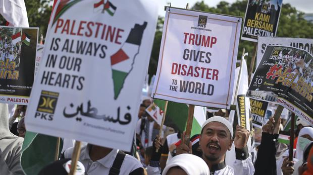 People outside the US Embassy in Jakarta hold posters during a rally against US president Donald Trump's decision to recognise Jerusalem as Israel's capital (AP/Dita Alangkara)