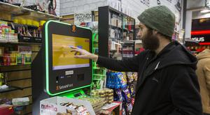 A customer uses a bitcoin machine in Piccadilly Circus in London (PA)