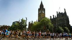 Runners pass Manchester Town Hall during The Great Manchester Run (PA)