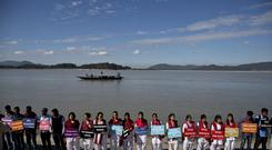 Students from India's northeastern Assam state hold placards by the Brahmaputra river during a protest against the contamination of the river in Gauhati, India (AP)