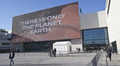 Participants walk past the main entrance of the One Planet Summit (AP)
