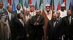 Turkey's President Recep Tayyip Erdogan, centre, flanked by Jordan's King Abdullah II, left and Palestinian President Mahmoud Abbas, right, at a photo-op prior to the opening session of the Organisation of Islamic Cooperation Extraordinary Summit in Istanbul (AP)