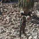 File picture of a Houthi Shiite fighter walking amid the rubble of a palace that was destroyed by Saudi-led airstrikes, in Sanaa, Yemen (AP)