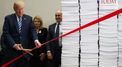 Mr Trump cut a ribbon or 'red tape' during an event on federal regulations at the White House (AP)