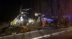 Rescue workers help after a school bus and a regional train collided in the village of Millas, southern France (Matthieu Ferri/France Bleu via AP)