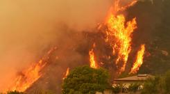 Flames from a wildfire rise behind a home in Santa Barbara, California (Santa Barbara County Fire Department/AP)