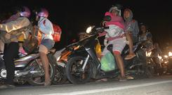 People flee on motorbikes amid fears of tsunami following an earthquake in central Java, Indonesia (AP Photo/Wagino)
