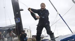 French sailor Francois Gabart sprays champagne as he celebrates his world record (AP)