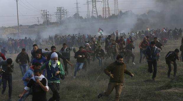 Palestinian protesters run for cover from tear gas fired by Israeli soldiers during clashes on the Israeli border (AP)