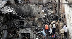 Indian fire officials inspect the burnt down shop in Mumbai (AP)