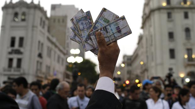 A protester holds up fake money during an anti-corruption march in Lima, Peru (AP Photo/Martin Mejia)