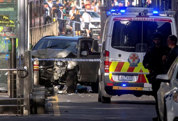 Australian police stand near a crashed vehicle after they arrested the driver who had ploughed into pedestrians at a crowded intersection near the Flinders Street train station in central Melbourne, Australia, yesterday. Photo: Reuters