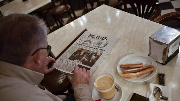 A man reads a Spanish newspaper featuring the results of the Catalan regional election while taking breakfast in Pamplona (AP)