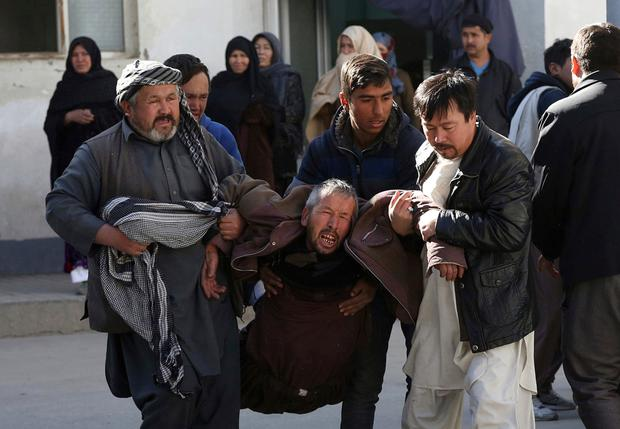 A distraught man is carried following a suicide attack in Kabul. Photo: Rahmat Gul/AP Photo