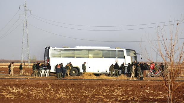 Syrian government forces stand next to a bus waiting to evacuate Syrian militants and their families from Beit Jin village, in the southern province of Daraa (Sana via AP)