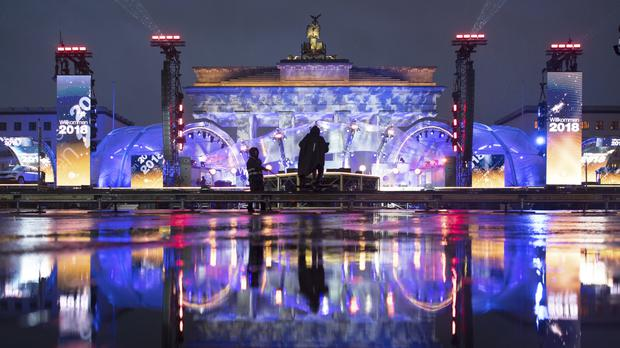 The illuminated Brandenburg Gate reflects in a puddle during a rehearsal prior to the New Year's Eve party in Berlin (Ralf Hirschberger/dpa via AP)