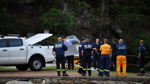 An officer carrying a piece of debris recovered from a seaplane that crashed into the Hawkesbury River