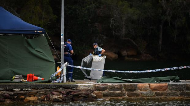 An officer carrying a piece of debris recovered from a seaplane that crashed into the Hawkesbury River in New South Wales (AAP/PA)