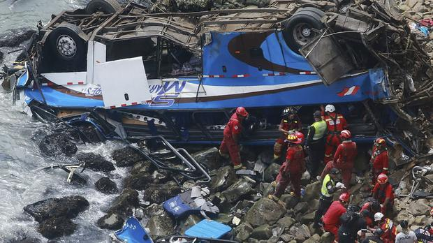 Rescuers at the site where a bus plunged off a coastal road