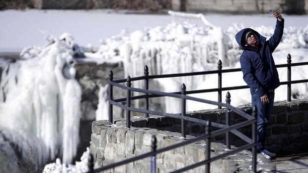 Someone captures a selfie in front of the partially frozen falls at the Paterson Great Falls National Historical Park in New Jersey (AP)