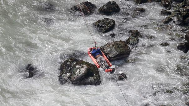 An injured man is transported over water from the site of the crash (AP)