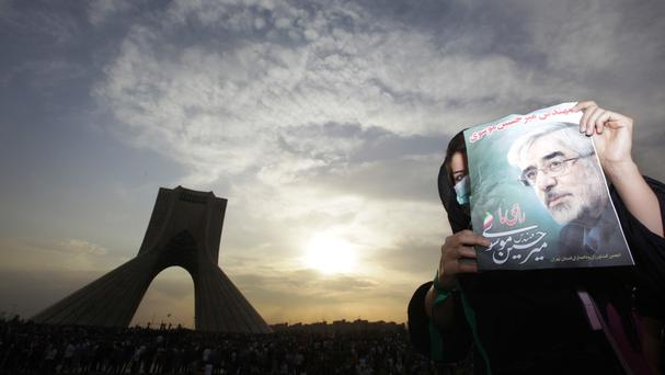 In an image from the summer of 2009, a female demonstrator holds up a poster of leading opposition presidential candidate Mir Hossein Mousavi (AP)