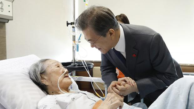 South Korean president Moon Jae-in, right, meets with Kim Bok-dong who was forced into sexual slavery by Japan's military during the Second World War (AP)