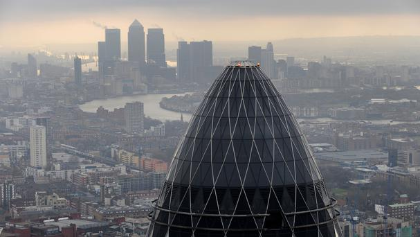 St Mary Axe also know as the 'Gherkin' and Canary Wharf at sunrise from the City of London (PA)