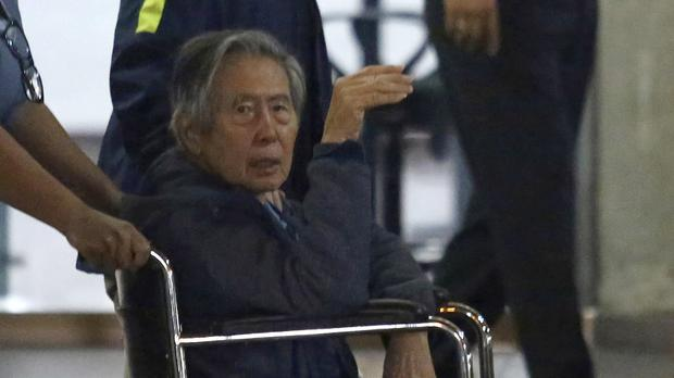 Former President Alberto Fujimori is wheeled out the hospital he was interned, in Lima, Peru. (AP Photo/Miguel Paredes)