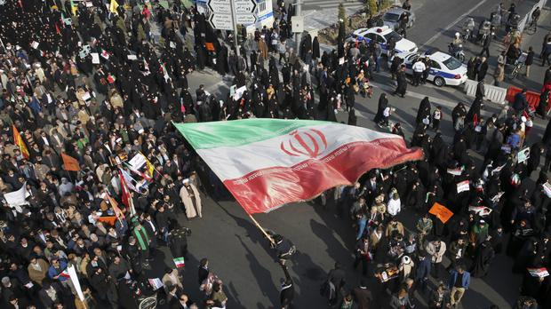 A demonstrator waves a huge Iranian flag during a pro-government rally in the northeastern city of Mashhad (Nima Najafzadeh/Tasnim News Agency via AP)
