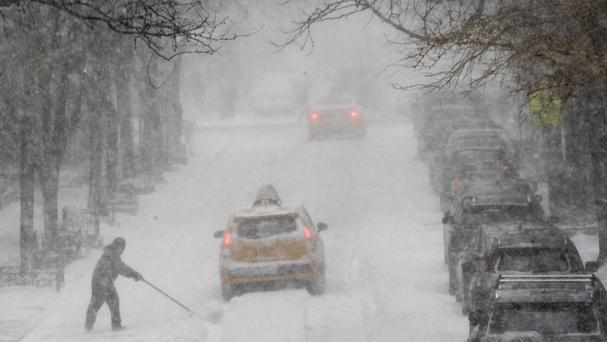 A man shovels snow in Manhattan after a massive winter storm swept from the Carolinas to Maine (AP Photo/Mary Altaffer)