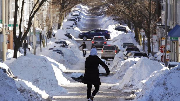 Mollie Lane carries a shovel-full of snow down the street to a pile while digging her car out in South Boston (AP)