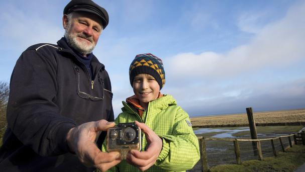 William Etherton and Roland Spreer hold a camera on the island of Suederoog, Germany (Christian Charisius/dpa via AP)