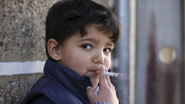 Fernando, a six-year-old, smokes a cigarette in the village of Vale de Salgueiro, northern Portugal, during Epiphany celebrations (AP)