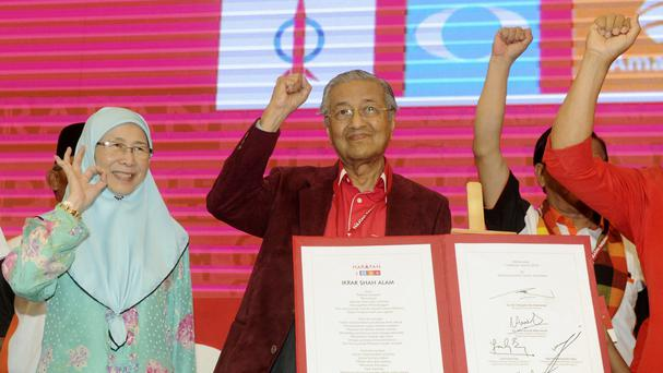 Malaysia former Prime Minister Mahathir Mohamad, centre, and Wan Azizah, wife of former Deputy Prime Minister Anwar Ibrahim, wave during a political opposition alliance meeting in Shah Alam, Malaysia. (AP Photo/Huey May)