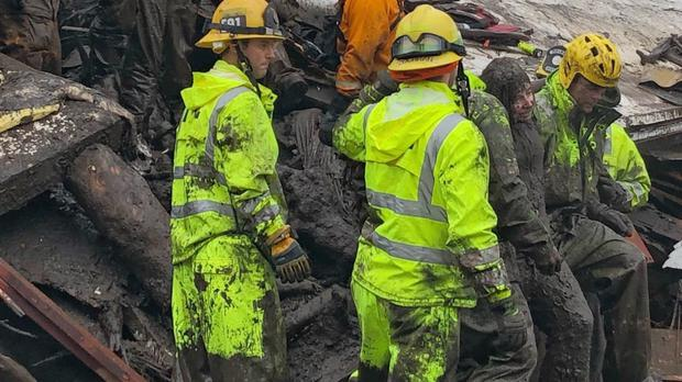 Firefighters rescue a 14-year-old girl from a destroyed home in Montecito (Santa Barbara County Fire Department/AP)