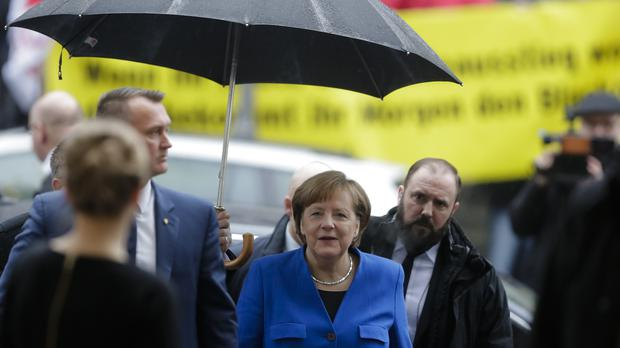 Angela Merkel (centre) arrives for exploratory talks about a new German government between her Christian Union block and the Social Democratic Party (Markus Schreiber/AP)