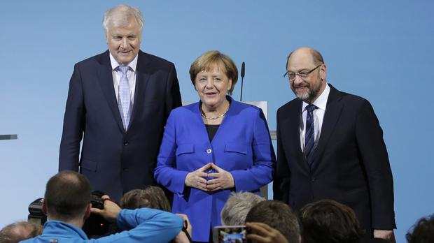 Angela Merkel is flanked by Bavarian governor Horst Seehofer and Social Democratic Party chairman Martin Schulz (AP)