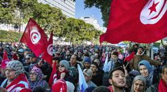 Tunisian people march with national flags during a rally to mark seven years since the revolution (AP)